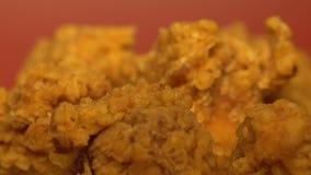 Poulet frit croustillant gras sur le fond rouge, concept malsain de nourriture, fin  banque de vidéos