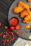 Poulet frit dans la chapelure avec de la sauce rouge des tomates d'un plat noir Images stock