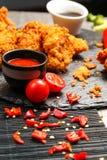Poulet frit dans la chapelure avec de la sauce rouge des tomates d'un plat noir Image libre de droits