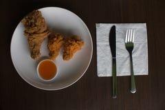 Poulet frit et sauce sur un petit déjeuner de faible luminosité blanche de plat ou de poulet sous-exposé et frit, poulet frit de  Photographie stock libre de droits