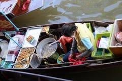 Poulet frit et vendeur de pommes frites s'asseyant sur son bateau dans le canal au marché de flottement de Damnoen Saduak photos stock