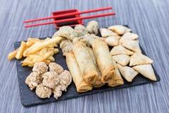 Poulet frit, gyozas, pommes frites, viande et boules de champignons sur une table en bois photos libres de droits