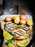 Poulet grillé avec des pommes de terre et des herbes sur le fond en bois Image libre de droits