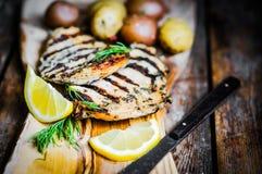 Poulet grillé avec des pommes de terre et des herbes sur le fond en bois Images stock