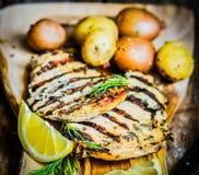 Poulet grillé avec des pommes de terre et des herbes sur le fond en bois Image stock