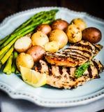 Poulet grillé avec les pommes de terre et l'asperge sur le fond en bois Photos libres de droits