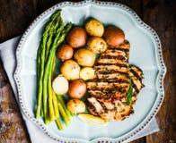 Poulet grillé avec les pommes de terre et l'asperge sur le fond en bois Image stock