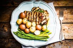 Poulet grillé avec les pommes de terre et l'asperge sur le fond en bois Photos stock