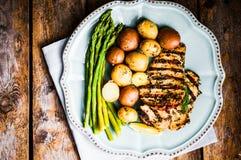 Poulet grillé avec les pommes de terre et l'asperge sur le fond en bois Photo libre de droits