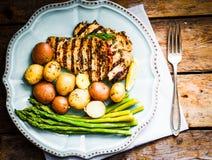 Poulet grillé avec les pommes de terre et l'asperge sur le fond en bois Images stock