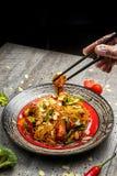 Poulet grillé d'un plat noir, situé à côté des légumes, des poivrons rouges et des baguettes photos libres de droits