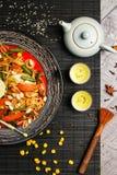 Poulet grillé d'un plat noir, situé à côté des légumes, des poivrons rouges et des baguettes photographie stock