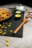 Poulet grillé d'un plat noir, situé à côté des légumes, des poivrons rouges et des baguettes images stock