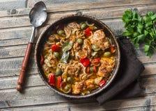 Poulet lent de cuiseur avec des olives et des poivrons doux dans la casserole sur le fond en bois, vue supérieure photos libres de droits
