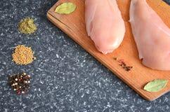Poulet sur un conseil en bois avec des épices Image libre de droits