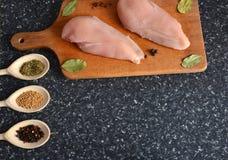 Poulet sur un conseil en bois avec des épices Photos stock