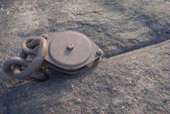 Poulie rouillée ancrée dans une roche Image stock