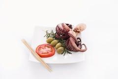 Poulpe avec la tomate, les olives et le romarin Photographie stock