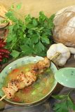 Poultry consomme with chicken skewer. Greens and parsley Stock Photo