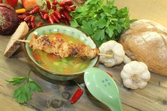 Poultry consomme with chicken skewer and greens. Poultry consomme with chicken skewer, vegetables and parsley Royalty Free Stock Photography