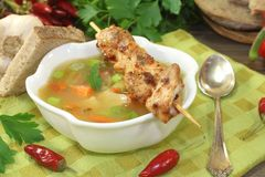 Poultry consomme with chicken skewers and parsley. On a napkin Stock Image