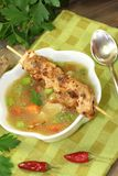 Poultry consomme soup with green and bread. Poultry consomme soup with green, smooth parsley and bread on a napkin Royalty Free Stock Images