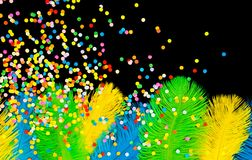 Poultry feathers and confetti are green, yellow and blue. Black. Poster for the carnival. Bright festive feathers in the color of the flag of Brazil Royalty Free Stock Photography