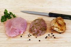 Poultry meat, raw, marinated and roasted on wooden board Stock Image
