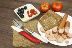 Poultry sausages on a wooden table, preparing home-made snacks. Royalty Free Stock Photography