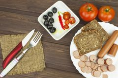 Poultry sausages on a wooden table, preparing home-made snacks. Royalty Free Stock Images