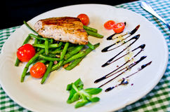 Poultry steak with green beans and tomatoes Stock Images