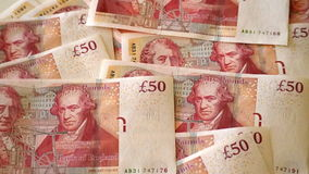 50 pound banknotes scattered on a table, with the faces of Matthew Boulton and James Watt. Detail of some 50 pound banknotes on a white table. Print or coin of Stock Photo