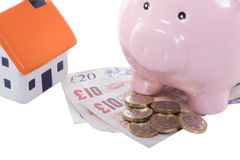 Pound bills and coins with a piggy bank and house. Pound bills and coins with a piggy bank and small model house in a concept of saving for your dream home Stock Images