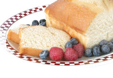 Pound Cake and Berries. A pound cake on a checkered plate with red raspberries and blueberries Stock Photography