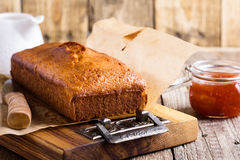 Pound cake on baking paper. Homemade pound cake on baking paper served with fruit jam ready to eat on rustic wooden table, delicious brunch or tea time Stock Photo