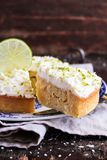 Pound cake with lemon, lime and freshly shredded coconut with cream cheese frosting, selective focus royalty free stock image