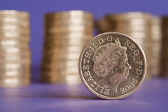 Pound coin. One shiny pound coin in focus, with piles of blurred coins in the background Royalty Free Stock Images