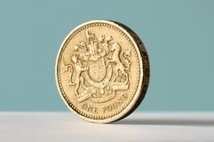 Pound coin. One pound coin stood up on blue background with copy space Stock Photography