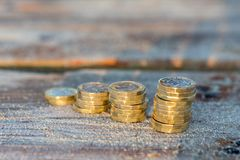 Pound Coin Stacks on Wooden Jetty, Money Royalty Free Stock Images
