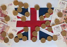 Pound coins and notes, United Kingdom over flag Stock Photos
