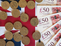 Pound coins and notes, United Kingdom over flag Royalty Free Stock Image