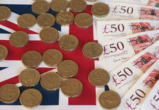 Pound coins and notes, United Kingdom over flag Stock Photo