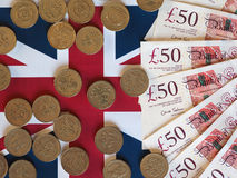 Pound coins and notes, United Kingdom over flag Stock Images