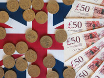 Pound coins and notes, United Kingdom over flag Royalty Free Stock Photo