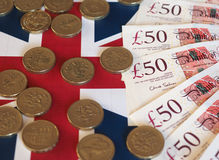 Pound coins and notes, United Kingdom over flag Royalty Free Stock Photography