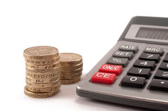 Pound coins. Stack of british pound coins next to a calculator Stock Photography