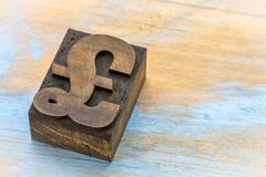 Pound symbol - wood type printing block. Pound currency symbol - vintage letterpress wood type printing block on wooden background stock photo