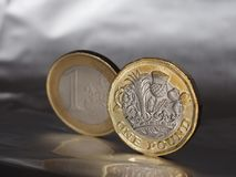 1 pound and 1 euro coin over metal background Stock Photos
