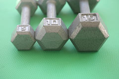5, 10 and 15 pound hand weights in a row Stock Images
