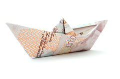 Pound money paper boat. Paper boat made from British pound banknotes over a white background stock images